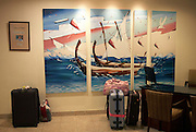 Tourist baggage is left at a hotel lobby reception desk against a mural showing traditional Maldives dhoni fishing boats