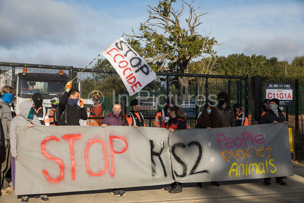 Environmental activists from HS2 Rebellion stand holding a banner to block a gate providing access to a site for the HS2 high-speed rail link on 12 September 2020 in Harefield, United Kingdom. Anti-HS2 activists continue to try to prevent or delay works on the controversial £106bn HS2 high-speed rail link in the Colne Valley where thousands of trees have already been felled.