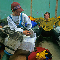 Young Inuit guides tickle Alex Lowe's foot as he exercises while storm-bound in hut on Canada's Baffin Island.