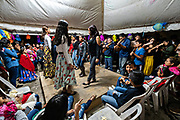 Zapateado dancers perform a traditional folk dance during a neighborhood Huapango in Santiago Tuxtla, Veracruz, Mexico. The dance involves dancers striking their shoes on a wooden platform while a large group of musicians play string instruments. The gatherings take part in the Los Tuxtlas mountain villages for single people to meet.