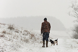 © Licensed to London News Pictures. 18/01/2019. Builth Wells, Powys, Wales, UK. A man walks a dog in a wintry landscape on the high moorland of the Mynydd Epynt range near Builth Wells in Powys, Wales, UK Heavy snow hits Powys Wales, UK. credit: Graham M. Lawrence/LNP