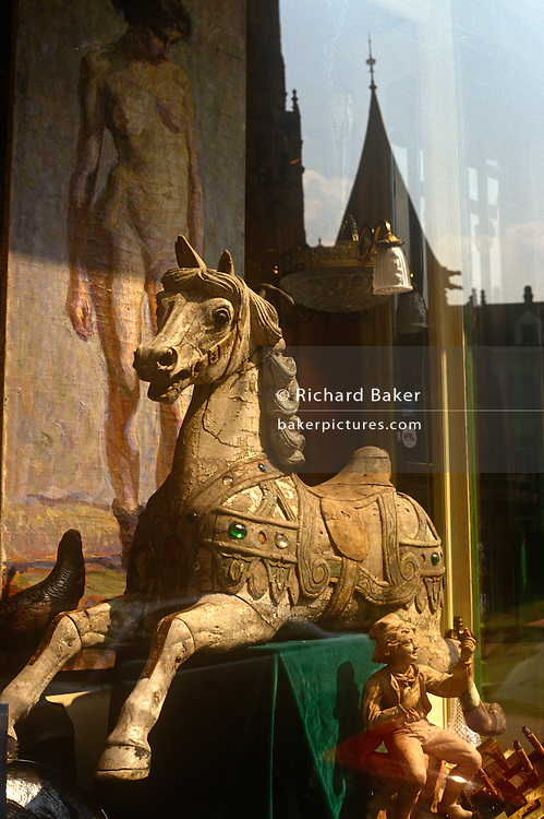Antique shop window and background reflections in the Place du Grand Sablon, Brussels. A rocking horse, a mural and small rural figurine can be seen in the sunlit window with a middle-age steeple reflected in the background. Place du Grand Sablon is a beautiful architectural square with houses from the 16th to the 19th century. It is home to antiques shops, typical restaurants and chocolatiers.