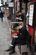 Two Asian workers from a restaurant in the West End both hold cigarettes while looking at content on their phones, on 16th January 2019, in London, England.