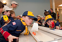Alex Cheek and Christian Blais test their wind as they sail their vessels during the 2nd annual Rain Gutter Regatta for Boy Scout Pack 243 at the Gilford Community Center Monday evening.  (Karen Bobotas/for the Laconia Daily Sun)
