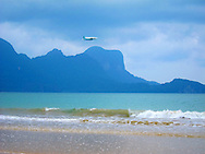Airplane flies over turquoise waters of El Nido with mountains rising up in background, Palawan, Philippines, Southeast Asia