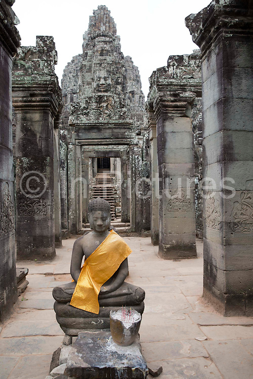 A stone statue of Buddha with a yellow tunic material draped over his shoulder in a walkway leading to the Bayon Temple in the ancient Angkor Thom, Siem Reap Province, Cambodia, South East Asia.