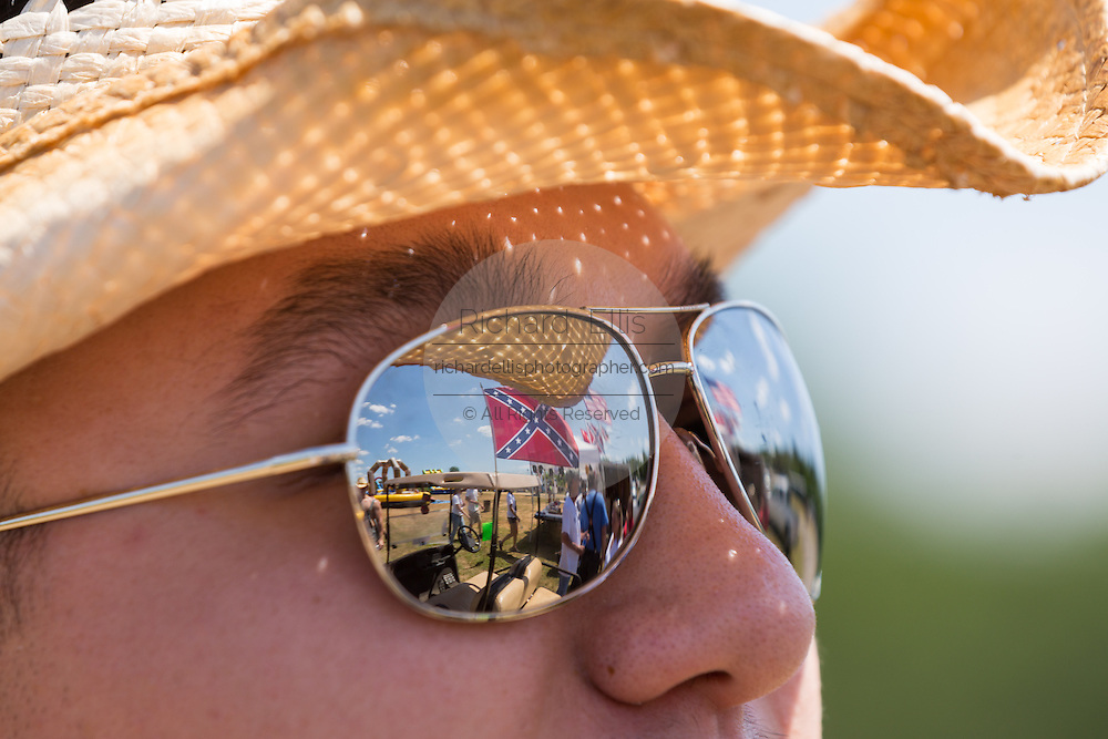 A confederate flag is reflected in the mirror sunglasses of a young man during the 2015 National Red Neck Championships May 2, 2015 in Augusta, Georgia. Hundreds of people joined in a day of country sport and activities.