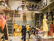 """12 NOVEMBER 2012 - BANGKOK, THAILAND:   A workshop for Buddhas on Bamrung Muang Street in Bangkok. Thanon Bamrung Muang (Thanon is Thai for Road or Street) is Bangkok's """"Street of Many Buddhas."""" Like many ancient cities, Bangkok was once a city of artisan's neighborhoods and Bamrung Muang Road, near Bangkok's present day city hall, was once the street where all the country's Buddha statues were made. Now they made in factories on the edge of Bangkok, but Bamrung Muang Road is still where the statues are sold. Once an elephant trail, it was one of the first streets paved in Bangkok. It is the largest center of Buddhist supplies in Thailand. Not just statues but also monk's robes, candles, alms bowls, and pre-configured alms baskets are for sale along both sides of the street.    PHOTO BY JACK KURTZ"""