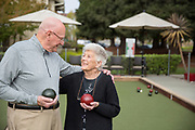A couple looking at each other while playing bocce ball
