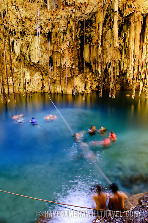 Swimmers enjoy the crystal clear waters of  Cenote X'kakah near Valladolid (also near Dzitnup). Part of the Yucatan's massive network of underground waterways that pass through the porous limestone, Cenote X'kakah is a popular underground swimming hole. It has a small opening in the ceiling that lets in light, fresh air, and even a little rain, and impressive stalactites hanging from the ceiling. The water temperature is a constant 76 degrees fahrenheit year round.