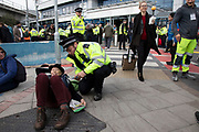 Police read section 14 notice and arrest an elderly female protester during Extinction Rebellion disruption outside City Airport on 10th October 2019 in London, England, United Kingdom. The protest is against the climate and pollution impact of the government's plans for airport expansion which will potentially double the amount of flights coming from City Airport. Extinction Rebellion is a climate change group started in 2018 and has gained a huge following of people committed to peaceful protests. These protests are highlighting that the government is not doing enough to avoid catastrophic climate change and to demand the government take radical action to save the planet.