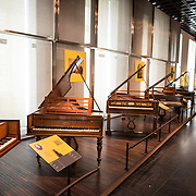 Pianos on display at the Musical Instrument Museum in Brussels. The Musee des Instruments de Musique (Musical Instrument Museum) in Brussels contains exhibits containing more than 2000 musical instruments. Displays include historical, exotic, and traditional cultural instruments from around the world. Visitors to the museum are given handheld audio guides that play musical demonstrations of many of the instruments. The museum is housed in the distinctive Old England Building.