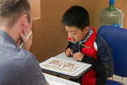Asian student and teacher working on problems in a workbook in class.