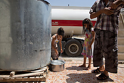 © Licensed to London News Pictures. Hamdaniyah, Iraq. 26/07/2014.  Christian refugee Dilar Minowar Salim, 9, watches as her sister Rania (5) fills a container after being resupplied with fresh drinking water by Kurdish Zeravani soldiers at the partially built home they share with 15 other family members in Hamdaniyah, Iraq. Dilar and Rania left Mosul on Friday the 18th of July with their family when Islamic State fighters issued an ultimatum to the city's Christian community. When the family left they were forced to pay a tax for their car, their elder brother (19) was threatened at knifepoint to ensure they handed over all of their possessions including family photographs.<br /> <br /> <br /> Having taken over Mosul Iraq's second largest city in June 2014, fighter of the Islamic State (formerly known as ISIS) have systematically expelled the cities Christian population. Despite having been present in the city for more than 1600 years, Christians in the city were given just days to either convert to Islam, pay a tax for being Christian or leave; many of those that left were also robbed at gunpoint as they passed through Islamic State checkpoints.. Photo credit : Matt Cetti-Roberts/LNP