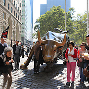 Tourists take pictures with The Charging Bull Monument  and Landmark, Outdoor Sculpture, and Public Art, <br /> Bowling Green (Broadway & Morris St), New York City, USA. 16th September 2014. Photo Tim Clayton