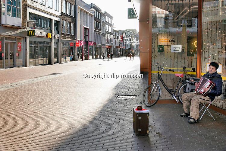 Nederland, Nijmegen, 18-12-2020 Lockdown in Nederland. De niet essentiele winkels zijn dicht. Een straatmuzikant speelt accordeon bij de Jumbo city La Place.Het is stil en leeg in de stad.Foto: ANP/ Hollandse Hoogte/ Flip Franssen