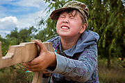 A boy participating to the ultra-nationalistic Azovets children's camp is struggling to hold the correct position with his wooden rifle, on the banks of the Dnieper river in Kiev, Ukraine's capital.