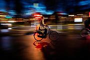 Een vrouw fietst 's avonds door Utrecht. De straten zijn nat van de regen.<br /> <br /> A woman cycles in Utrecht on an evening. The streets are wet due to the rain.