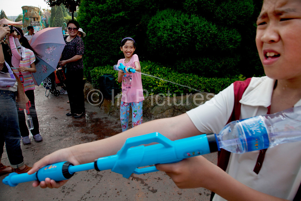 Children having a water fight with water pistols and guns. Soaking wet they are having great fun and laughing as they chase one another. Happy Valley Beijing is an amusement park in Beijing, China built and operated by Beijing OTC, which is part of the Shenzhen OCT Holding Group. The park, which is located in the east of Beijing, opened in July, 2006. It is one of four theme parks in the brand chain. Similar in style with the Disney land park, Happy Valley Beijing also featured distinctive landscapes and themes throughout the resort along with featured rides within the different themes. In total there are more than 40 rides.