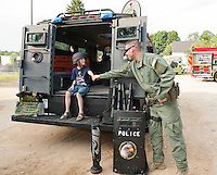 """Bobby Follansbee learns about the """"Bear Cat"""" from Special Operations Officer Kris Klootz during Belmont Police Department's National Night Out Tuesday evening.  (Karen Bobotas/for the Laconia Daily Sun)"""