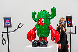 "© Licensed to London News Pictures. 29/10/2020. LONDON, UK. A staff member poses with a cactus artwork and viewing robots. Preview of ""Philip Colbert: Lobsteropolis"", a new exhibition at the Saatchi Gallery in Sloane Square.  The new lockdown inspired exhibition is available to view remotely via robot.  The exhibition (29 October – 29 November) is the largest UK survey of Colbert's universe to date and includes unseen large-scale paintings and sculptures.  Photo credit: Stephen Chung/LNP"