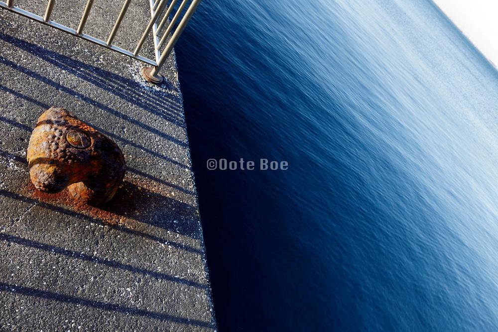 rusty bollard on fenced off pier