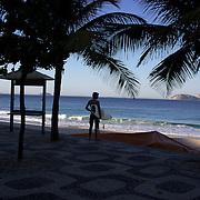 A surfer survey's the waves at Praia do Arpoador, Arpoador beach, Rio de Janeiro,  Brazil. 12th July 2010. Photo Tim Clayton..