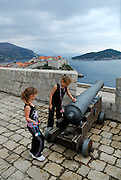 Two children (9 years old, 5 years old) playing with cannon on Fortress Lovrinjenac (Fort of Saint Lawrence), overlooking Adriatic Sea, Dubrovnik old town and Island of Lokrum. Dubrovnik old town, Croatia