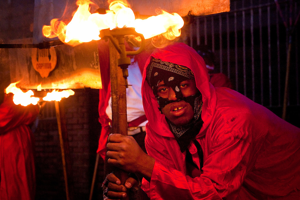One of the oldest traditions of Mardi Gras, Flambeaux carry kerosene torches on the day before Mardi Gras in the Krewe of Orpheus parade as it rolls through the Uptown area of New Orleans, Louisiana, USA, 23 February 2009.