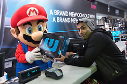 © licensed to London News Pictures. London, UK 29/11/2012. A Super Mario mascot handing out the first Nintendo Wii U in London as Nintendo launching its latest gaming console, Wii U at HMV Store in Oxford Street, London. Photo credit: Tolga Akmen/LNP