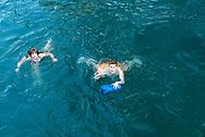 Bern, Switzerland - August 16, 2018: Two people float down the Aare River, a popular summer activity in Bern, Switzerland.