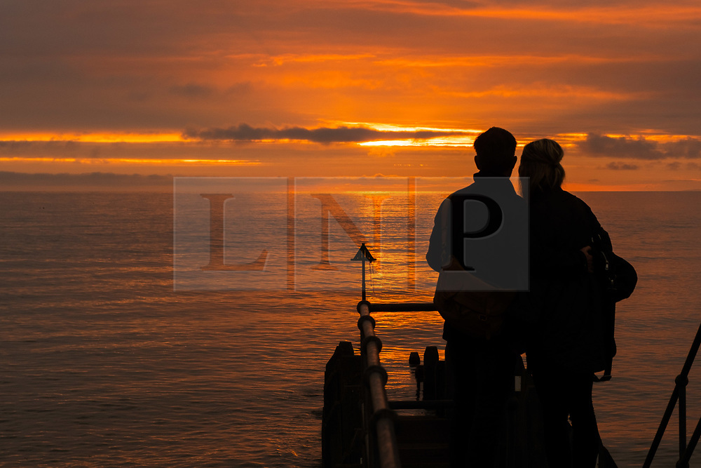 ©Licensed to London News Pictures<br /> 18/06/2019 Aberystwyth, UK.<br /> After day of showery rain and grey overcast skies, a couple are silhouetted as they watch the fiery sunset filling the sky over Cardigan Bay at Aberystwyth on the west Wales coast. Photo credit: Keith Morris/LNP