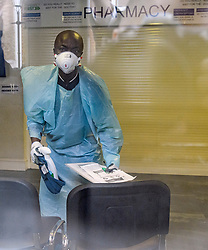 © Licensed to London News Pictures. 13/02/2020. London, UK. a Worker in a medical mask cleaning inside Ritchie Street Health Centre in Islington which has closed due to the Coronavirus COVID-19 outbreak, according to a notice on its website. Photo credit: Ben Cawthra/LNP