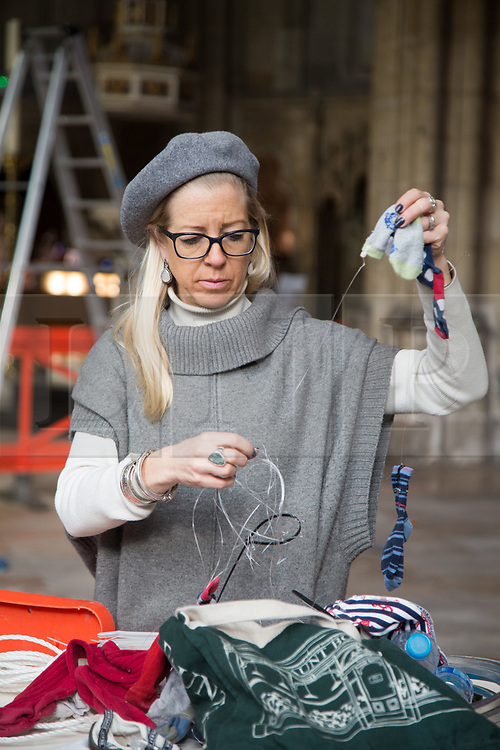 """@Licensed to London News Pictures 22/02/2018. Canterbury, UK. Artist Arabella Dorman makes the final adjustments to her installation """"Suspended"""" in the nave of Canterbury Cathedral in Kent today. This evocative artwork highlights the plight of refugees around the world and is made up of hundreds of items of refugee clothing found mainly on the beaches of the Greek Island of Lesbos. Photo credit: Manu Palomeque/LNP"""