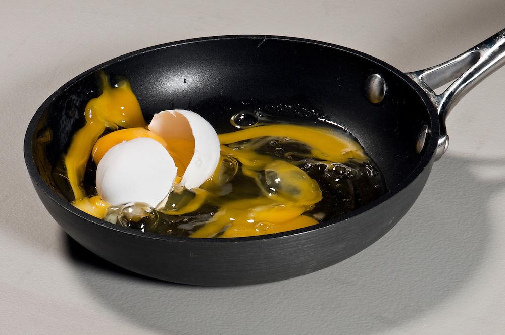 Eggs falling and splashing into pan preparing an omelette.