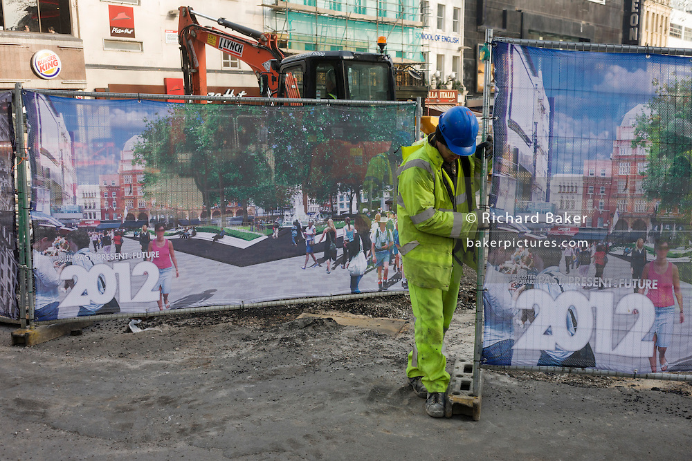 London contractor workmen close construction site screens, showing a new development at Leicester Square for 2012.