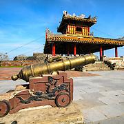 A cannon in the foreground, with restored pagoda in the background outside the moat at the Imperial City in Hue, Vietnam. A self-enclosed and fortified palace, the complex includes the Purple Forbidden City, which was the inner sanctum of the imperial household, as well as temples, courtyards, gardens, and other buildings. Much of the Imperial City was damaged or destroyed during the Vietnam War. It is now designated as a UNESCO World Heritage site.
