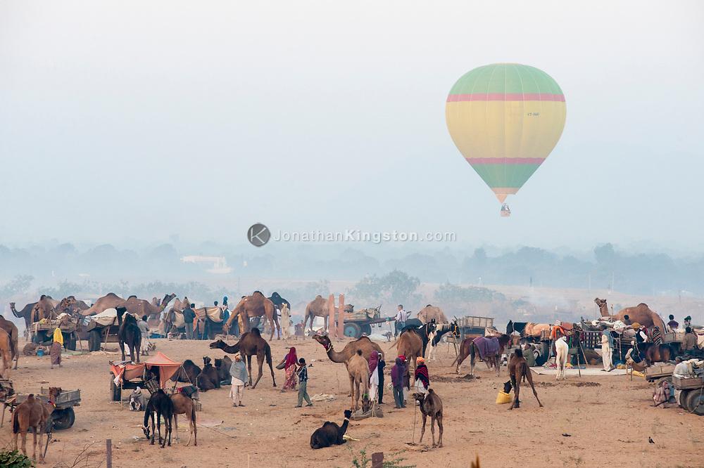 A hot air balloon hangs in the air above the Pushkar camel fair.
