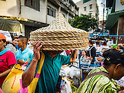 30 AUGUST 2016 - BANGKOK, THAILAND:  A person collects baskets after others  leave the Poh Teck Tung Shrine with baskets full of food and clothing on the last day of Hungry Ghost Month in Bangkok. Chinese temples and shrines in the Thai capital host food distribution events during Hungry Ghost Month, during the 7th lunar month, which is usually August in the Gregorian calendar.         PHOTO BY JACK KURTZ