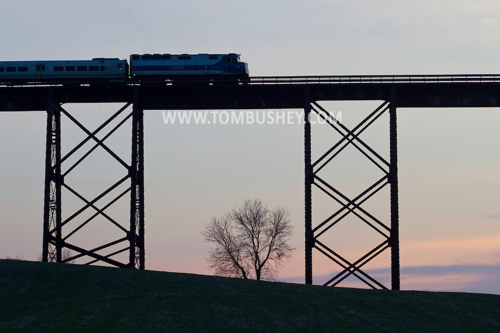 Salisbury Mills, New York - A Metro North passenger train crosses  the Moodna  Viaduct railroad trestle on April 13, 2014. The bridge was constructed between 1904 and 1908 by the Erie Railroad and was opened for service in January 1909. The steel structure is the highest and longest railroad trestle east of the Mississippi River.
