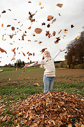 Happy girl throwing autumn leaves