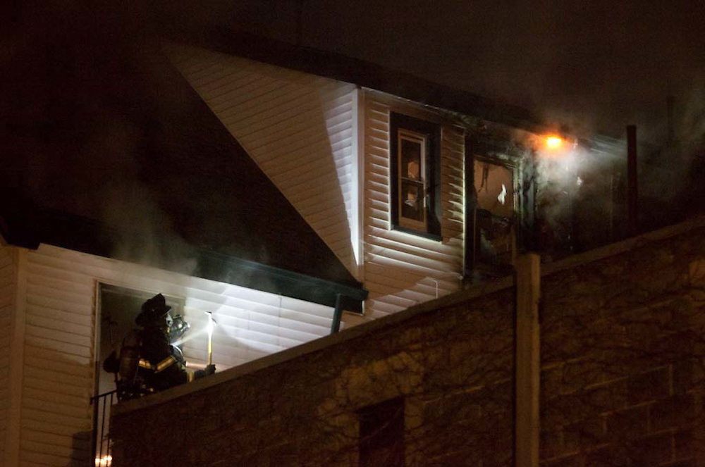 Somerville, MA 02/06/2012.A firefighter looks at a burning hot spot on the 3rd floor of a house that caught fire on Jacques St. on Monday evening..Wicked Local Photo by Alex Jones
