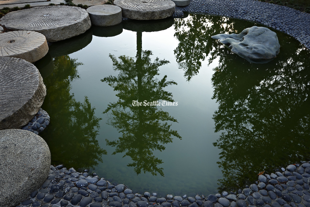 A still pond, rimmed in Chinese millstones and black pebbles, reflects the sky and majestic conifers. (Benjamin Benschneider / The Seattle Times)