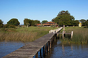 Jetty cming from farm onto the lake, showing farmhouse in the background. Working Gaucho Fazenda in Rio Grande do Sul, Brazil.