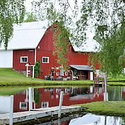 A Stark Red Farmhouse Reflects Off Of A Still Pond In Jordan River Valley, East Jordan Michigan
