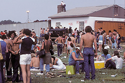 Folks going into The Grateful Dead Concert at Raceway Park, Englishtown NJ on 3 September 1977. Labor Day Weekend and on The Road into the Show. This shot taken outside the venue leading up to a gate which you can see here just to the left of center next to the Good Humor stand. Cropped Left of center of the original format.
