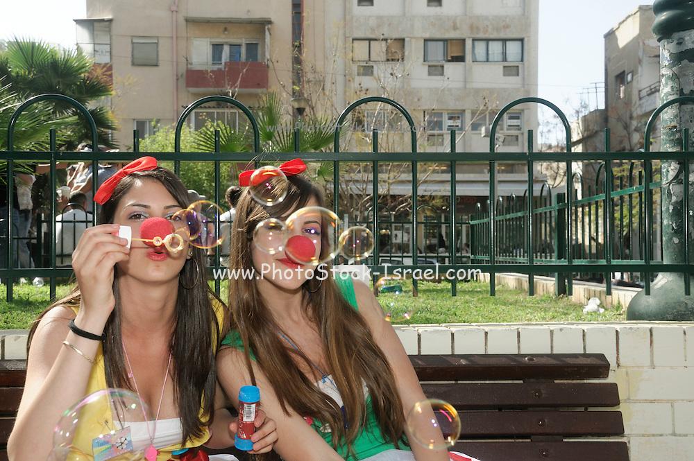 Israel, Tel Aviv, Purim celebration March 2008 teen clown blowing soap bubbles