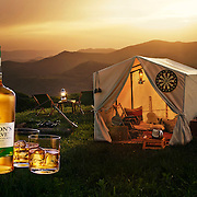 Bottle of Whiskey and two glasses with a tent and seats in the background perched on top of a hill range Ray Massey is an established, award winning, UK professional  photographer, shooting creative advertising and editorial images from his stunning studio in a converted church in Camden Town, London NW1. Ray Massey specialises in drinks and liquids, still life and hands, product, gymnastics, special effects (sfx) and location photography. He is particularly known for dynamic high speed action shots of pours, bubbles, splashes and explosions in beers, champagnes, sodas, cocktails and beverages of all descriptions, as well as perfumes, paint, ink, water – even ice! Ray Massey works throughout the world with advertising agencies, designers, design groups, PR companies and directly with clients. He regularly manages the entire creative process, including post-production composition, manipulation and retouching, working with his team of retouchers to produce final images ready for publication.