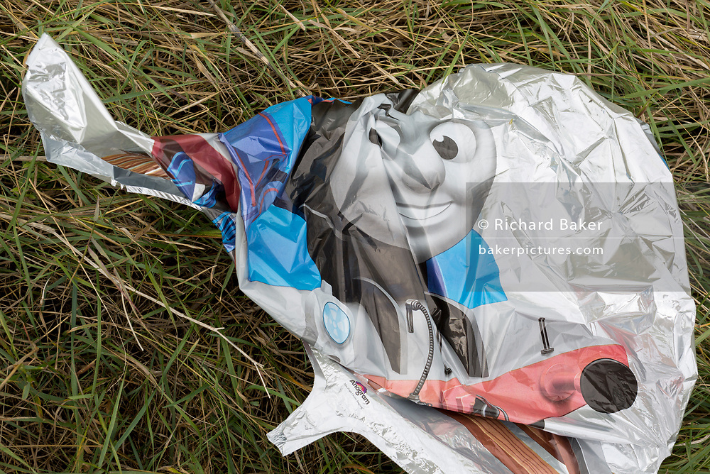 A detail of a child's deflated 'Thomas The Tank Engine' Anagram balloon that has landed, making it hazardous to wildlife, on marshland near Two Tree Island, at Leigh creek in Old Leigh, on 10th September 2019, in Leigh-on-Sea, Essex, England.
