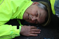 © Licensed to London News Pictures. 25/10/2021. London, UK. An Insulate Britain climate change activist with his head glued to the road an an attempt to block traffic on Bishopsgate in the City of London. The group have restarted their actions to block motorways and major roads causing disruption in the week before the COP26 climate meeting in Glasgow on 31/10/2021. Photo credit: Ben Cawthra/LNP